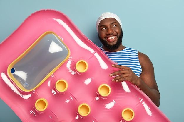 Joyeux homme afro heureux avec un sourire à pleines dents, détient un matelas gonflable, prêt à se détendre pendant la journée ensoleillée à la plage