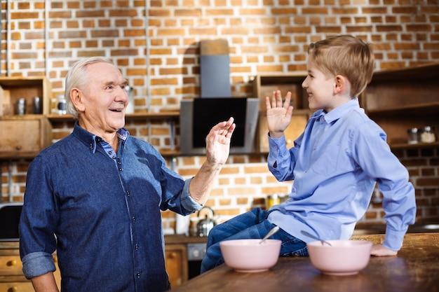 Joyeux homme âgé attentionné s'amusant avec son petit-fils en se tenant debout dans la cuisine