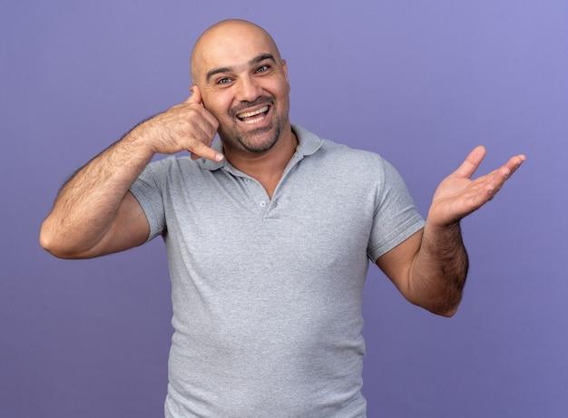 Joyeux homme d'âge moyen décontracté faisant un geste d'appel montrant une main vide isolée sur un mur violet
