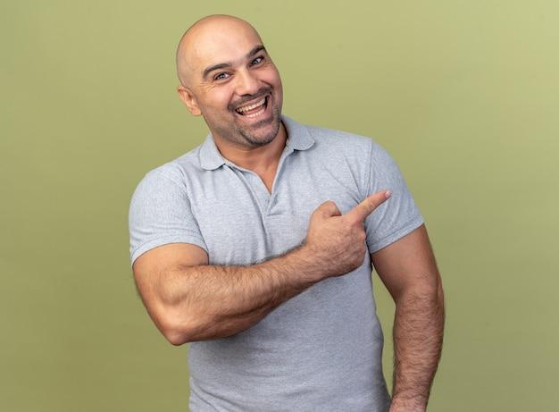 Joyeux homme d'âge moyen décontracté regardant l'avant pointant sur le côté isolé sur un mur vert olive