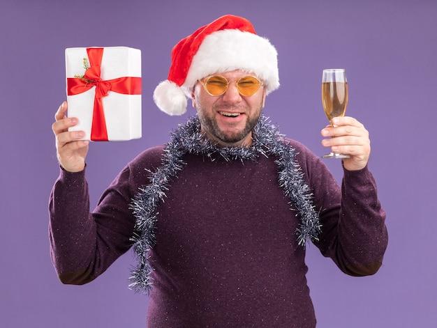 Joyeux homme d'âge moyen portant bonnet de noel et guirlande de guirlandes autour du cou avec des lunettes tenant un paquet cadeau et un verre de champagne en riant isolé sur mur violet
