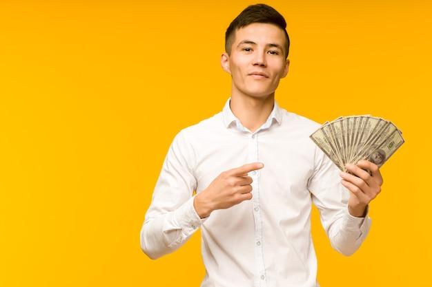 Joyeux homme asiatique dans une chemise blanche pointe un doigt sur des dollars d'argent sur fond jaune