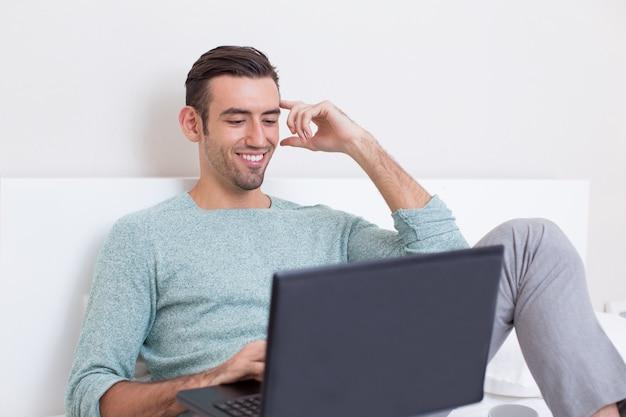 Joyeux homme assis confortablement avec un canapé avec un ordinateur portable