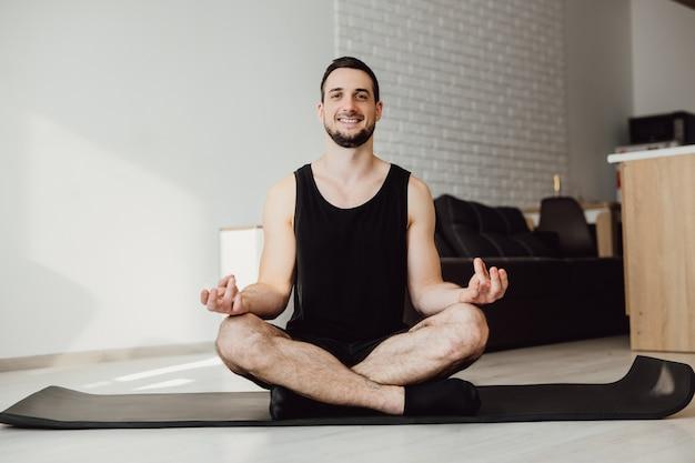 Joyeux homme assis en posture de lotus. concept de mode de vie sain. homme brune regardant la caméra, souriant et se sentant bien après la méditation. prenez soin de votre santé mentale.