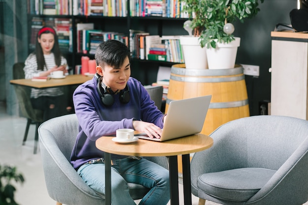 Joyeux homme assis avec une tasse de café et un ordinateur portable moderne. jeune femme relaxante près de l'étagère sur l'arrière-plan