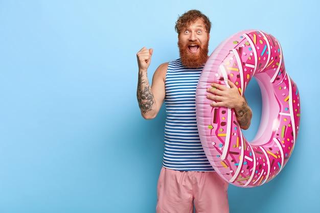 Joyeux homme aux cheveux rouges posant avec piscine de beignet flottant