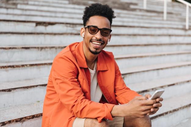 Joyeux homme bouclé à la peau foncée en veste orange et lunettes de soleil sourit largement, tient le téléphone et s'assoit dans les escaliers à l'extérieur