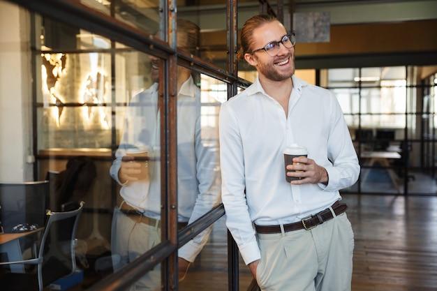 Joyeux homme caucasien à lunettes riant et buvant du café tout en s'appuyant sur un mur de verre au bureau