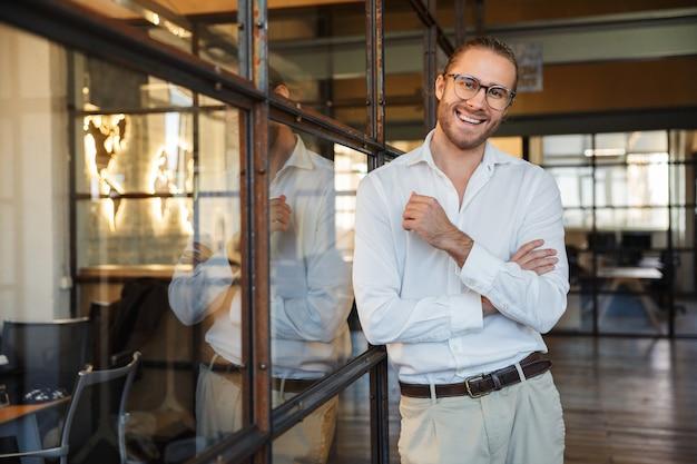 Joyeux homme caucasien à lunettes souriant tout en s'appuyant sur un mur de verre dans un bureau moderne
