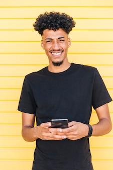 Joyeux homme ethnique utilisant un téléphone