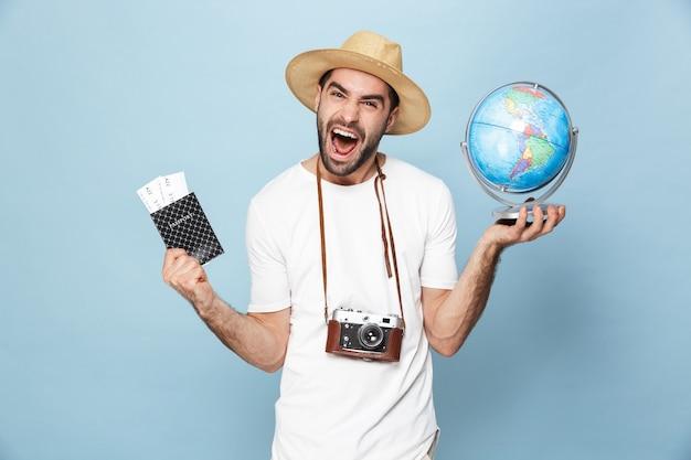 Joyeux homme excité portant un t-shirt vierge debout isolé sur un mur bleu, montrant un globe et un passeport avec des billets