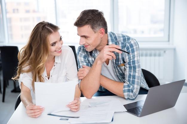 Joyeux homme et femme assis et flirtant lors d'une réunion d'affaires