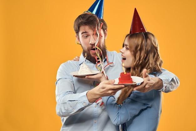 Joyeux homme et femme célébration anniversaire gâteau divertissement confettis fond jaune