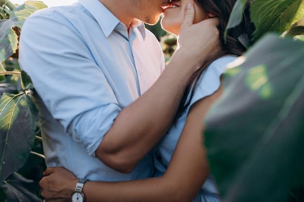 Joyeux homme et femme enceinte s'embrassent dans le champ
