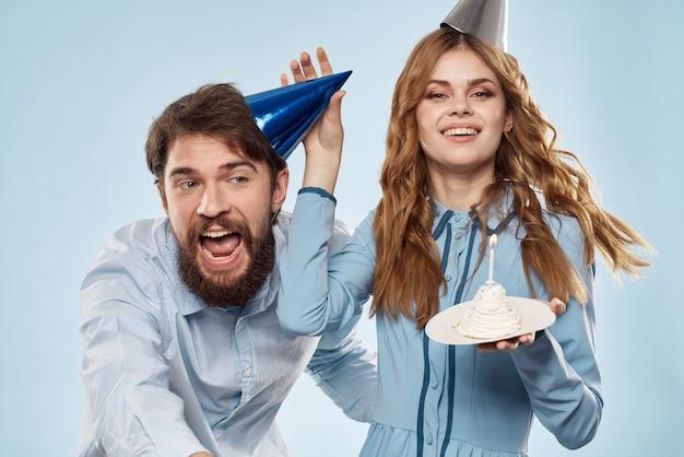 Joyeux homme et femme avec un gâteau dans une assiette fête corporative fond bleu