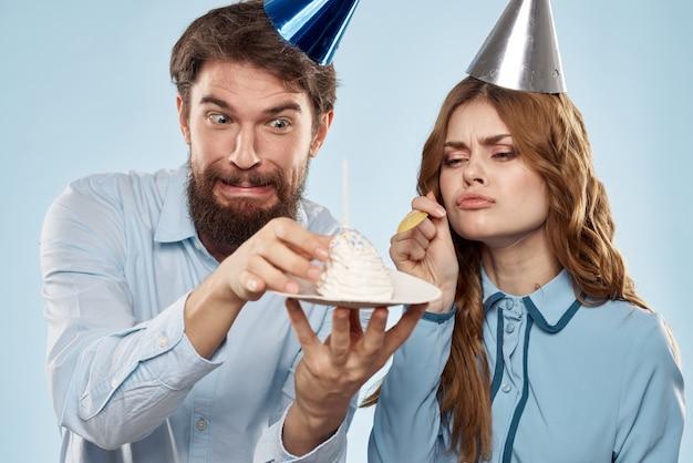 Joyeux homme et femme avec un gâteau dans une assiette de fête d'entreprise bleu
