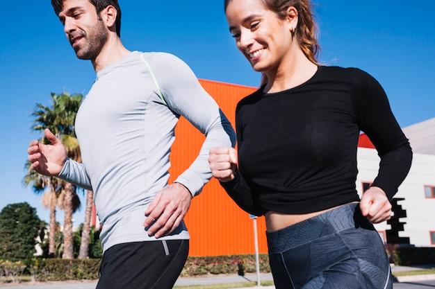 Joyeux homme et femme jogging ensemble