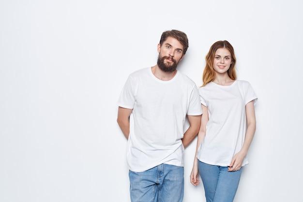 Joyeux homme et femme en t-shirts blancs et jeans design studio fond clair. photo de haute qualité