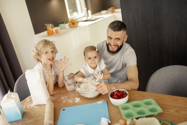 Joyeux homme heureux assis avec ses enfants