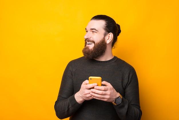 Joyeux homme hipster barbu debout sur un mur jaune à l'aide d'un smartphone et à la recherche de copyspace
