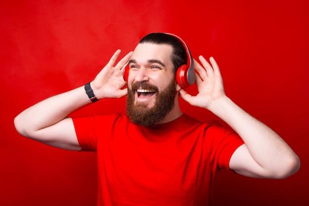 Joyeux homme hipster barbu écouter de la musique au casque sur mur rouge
