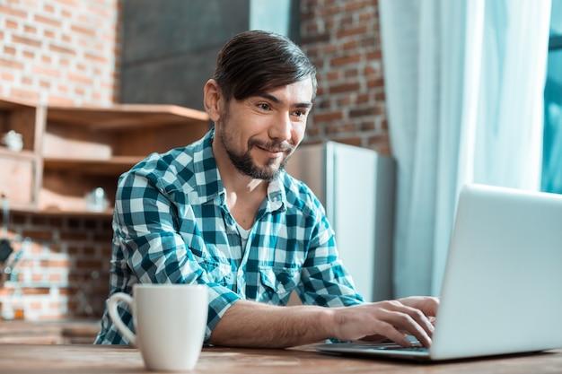 Joyeux homme intelligent positif assis devant l'ordinateur et souriant tout en travaillant à distance de la maison