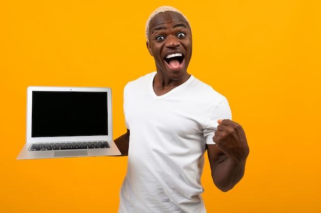 Joyeux homme noir américain avec un beau sourire blanc comme neige dans un t-shirt blanc avec un ordinateur portable avec une mise en page orange