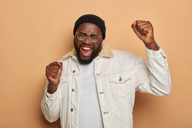 Joyeux homme noir insouciant danse avec les poings levés, porte des lunettes transparentes