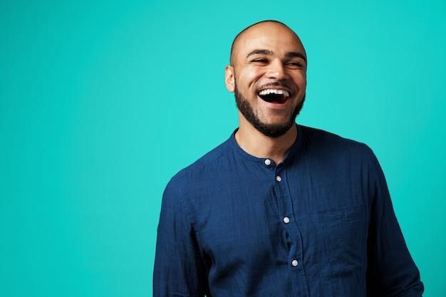 Joyeux homme à la peau sombre en riant sur fond turquoise