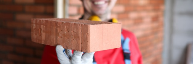Joyeux homme portant un casque jaune tenir la brique