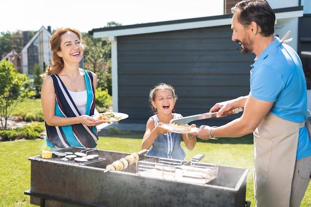 Joyeux homme positif servant de la nourriture tout en ayant un pique-nique avec sa famille