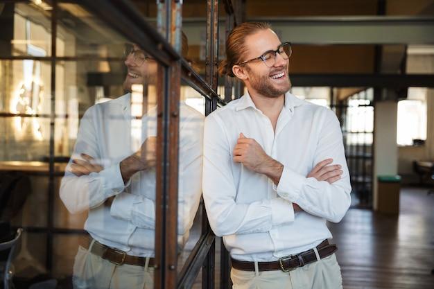 Joyeux homme de race blanche à lunettes en riant tout en s'appuyant sur un mur de verre dans un bureau moderne