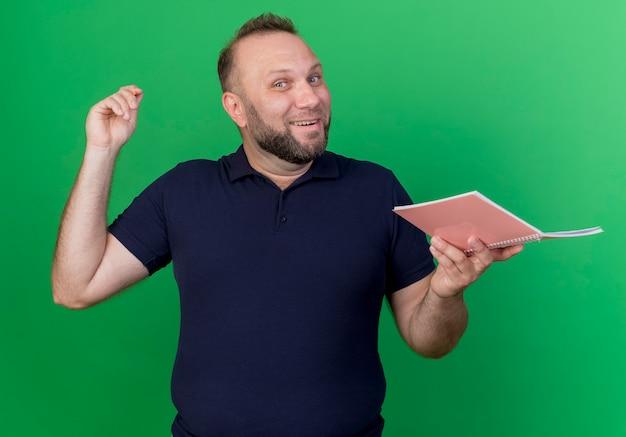 Joyeux homme slave adulte tenant un crayon et un bloc-notes à la recherche d'isolement sur le mur vert