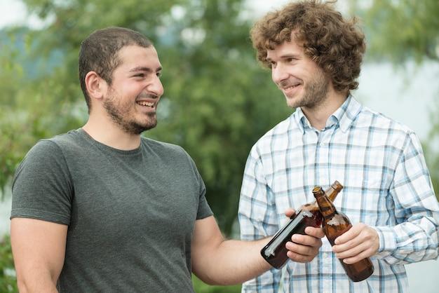 Joyeux hommes cliquetant des bouteilles de bière dans la nature