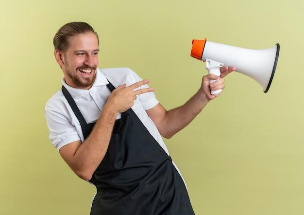 Joyeux jeune beau coiffeur tenant le haut-parleur à la recherche et pointant sur le côté isolé sur vert olive