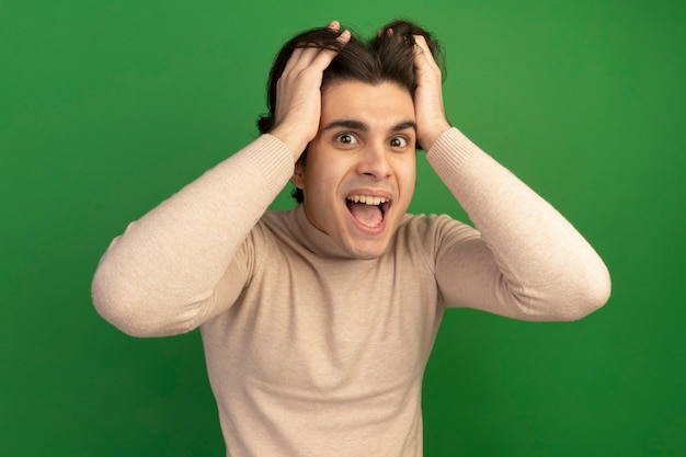 Joyeux jeune beau mec a attrapé la tête isolée sur un mur vert
