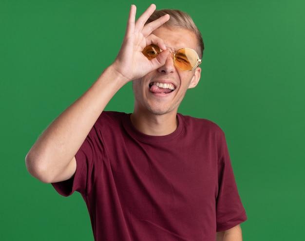 Joyeux jeune beau mec portant une chemise rouge et des lunettes montrant le geste de regard isolé sur le mur vert