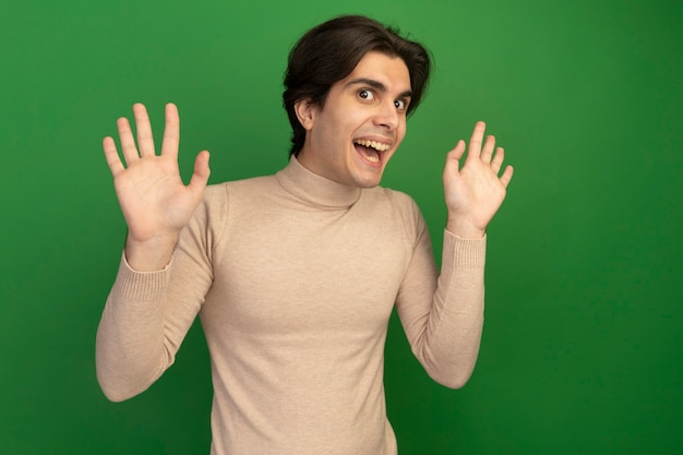 Joyeux jeune beau mec répandant les mains isolés sur le mur vert