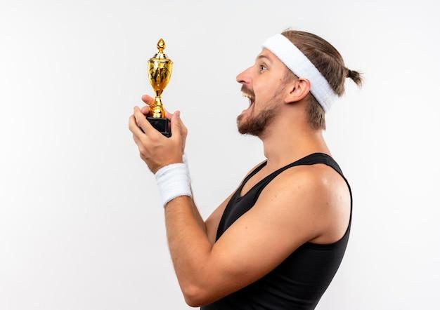 Joyeux jeune bel homme sportif portant un bandeau et des bracelets debout en vue de profil tenant la coupe du vainqueur isolée sur un mur blanc avec espace pour copie