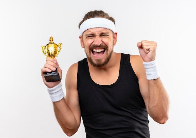 Joyeux jeune bel homme sportif portant un bandeau et des bracelets tenant la coupe du gagnant et serrant le poing isolé sur un mur blanc