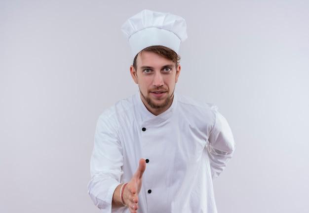 Un joyeux jeune chef barbu homme vêtu d'un uniforme de cuisinière blanc et hat stretching hand pour secouer pour accueillir quelqu'un sur un mur blanc