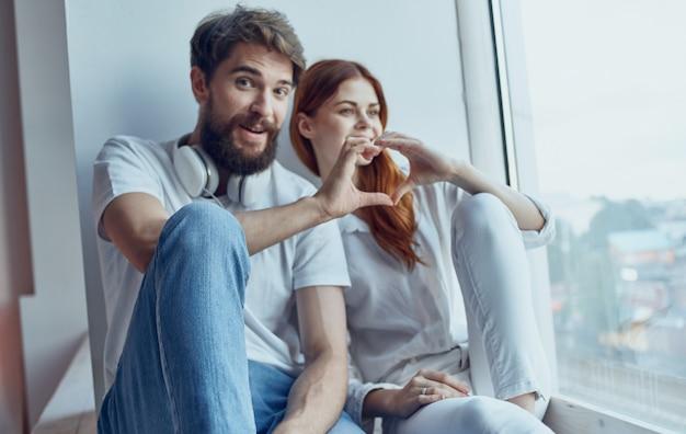 Joyeux jeune couple assis près de l'intérieur de la communication de la technologie de la fenêtre