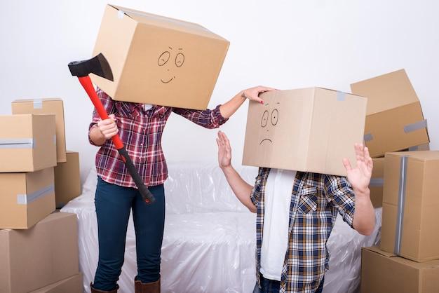 Joyeux jeune couple avec des boîtes en carton sur la tête.