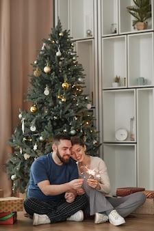 Joyeux jeune couple caucasien assis sur le sol contre un arbre décoré et allumant des cierges magiques à ch...