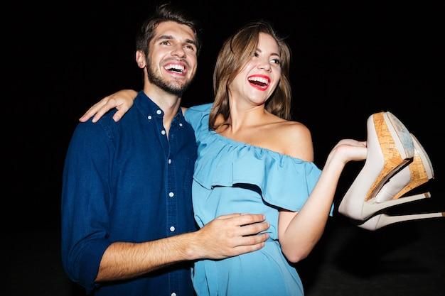 Joyeux jeune couple avec des chaussures dans les mains s'embrassant et s'amusant la nuit