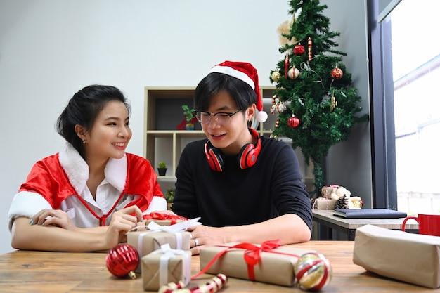 Joyeux jeune couple décorant des cadeaux de noël ensemble dans le salon.