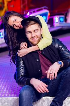 Joyeux jeune couple élégant étant ludique tout en visitant une arcade de parc d'attractions avec manèges