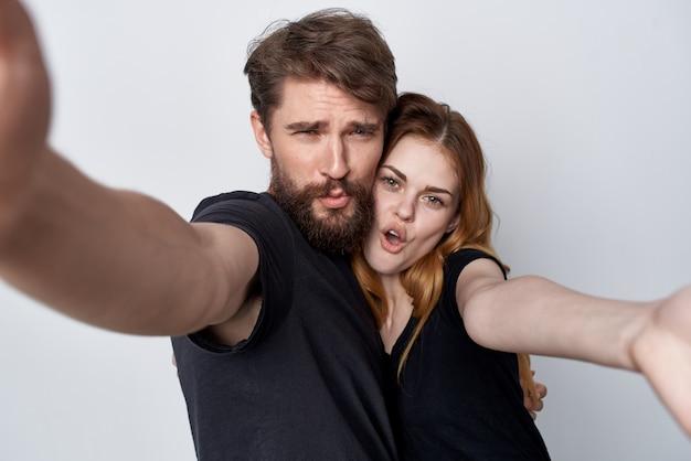 Joyeux jeune couple ensemble selfie communication émotions fond clair