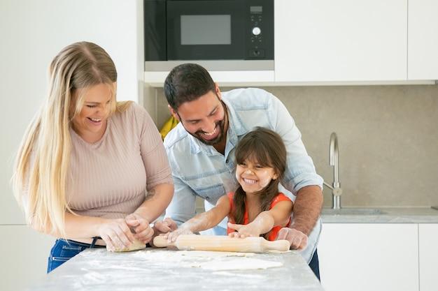 Joyeux jeune couple et fille avec de la poudre de fleur sur le visage en riant pendant la cuisson ensemble.