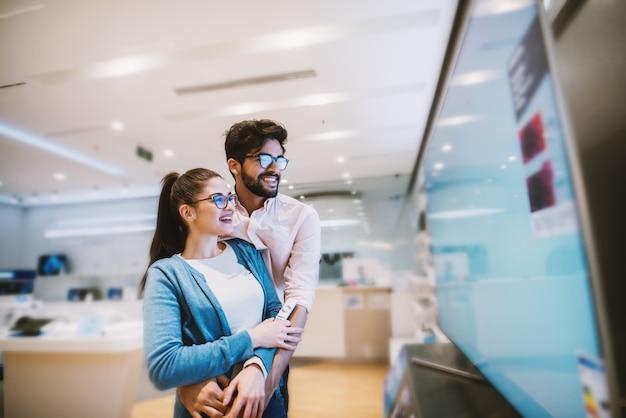 Joyeux jeune couple hipster attrayant vérifiant les téléviseurs à écran plasma dans le magasin électronique.